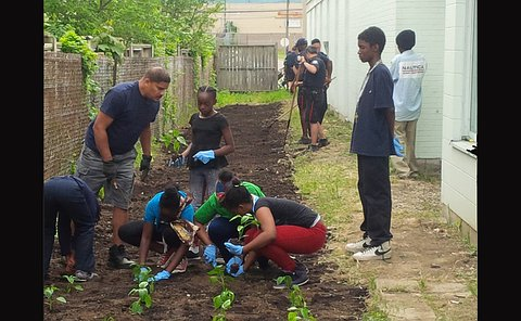 Adults, some in TPS uniform, with children put plants in a largely bare garden