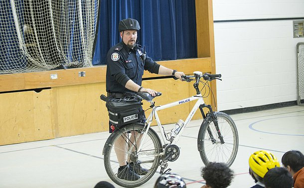A man in TPS uniform holding a bike in front of a group of children