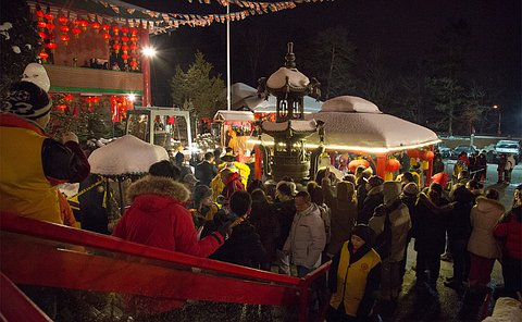 A group of people milling about an outdoor area with red lanterns