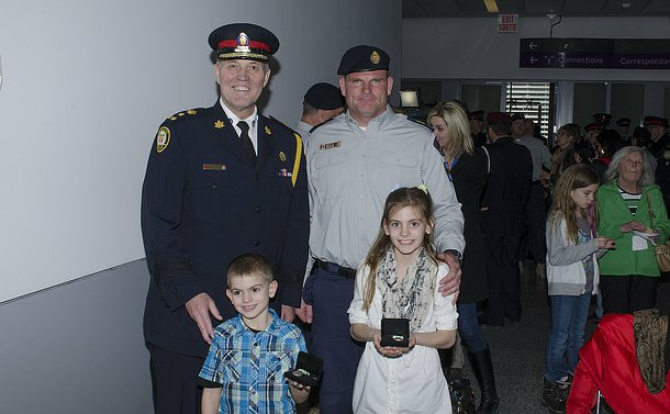 Two men in TPS uniform with two children holding medals