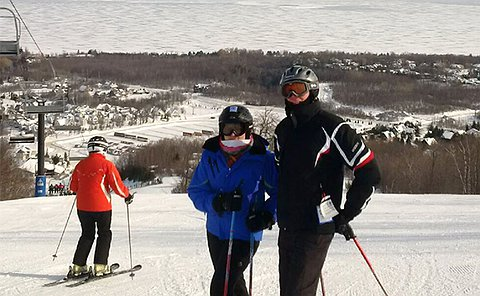 Two people on skis at the top of a ski run