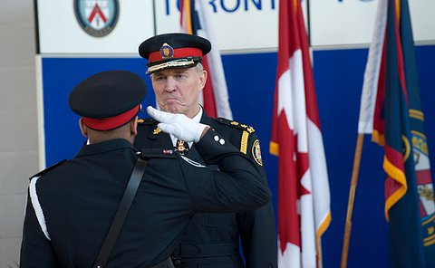 Back of man saluting the chief who is smiling and saluting him back