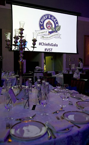 A formal table setting with a large screen with Chief's Gala logo