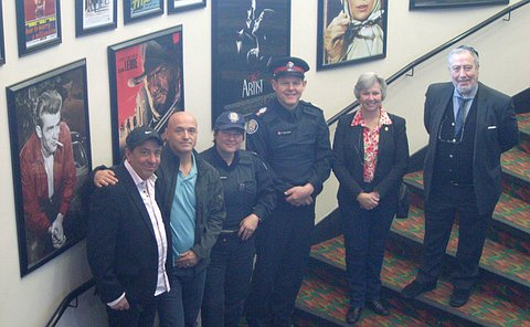 A group of people including a man and woman in TPS uniform on a staircase with movie posters in background