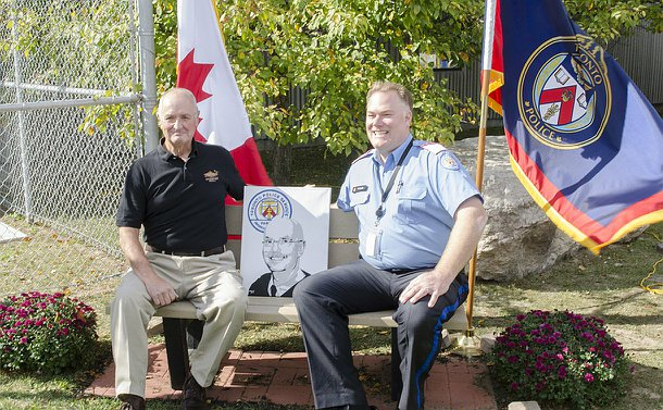 Two men, one in TPS Parking uniform sit on a bench with a portrait between them and a TPS flag and Canadian flag behind them