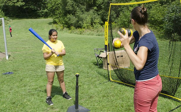 A girl holds a baseball bat in front of a tee holding a ball looking at a woman giving instruction