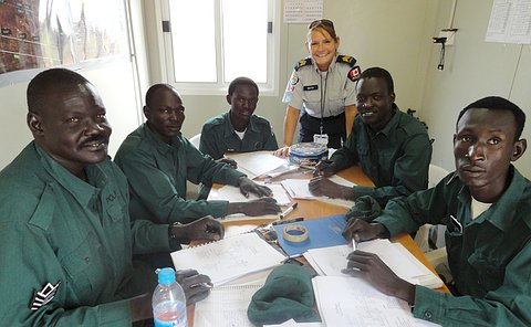 A group of men in green police uniforms sit a a long table with pencils and paper in front of them looking at the camera. A woman in a Toronto police uniform stands in the background