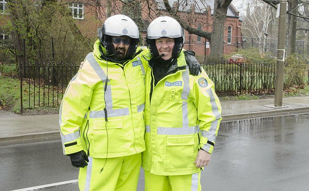 Close up of two policemen wearing bright yellow weather coveralls