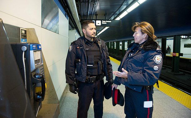 A man and woman in TPS uniform on a subway platform near a pay phone