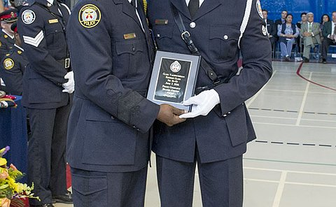 Two men in TPS uniform holding a plaque