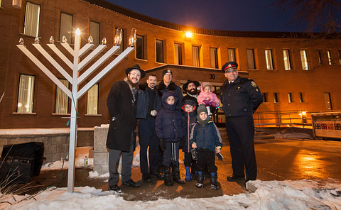 Three men in TPS uniform with two other men and three children by a large menorah outside a building