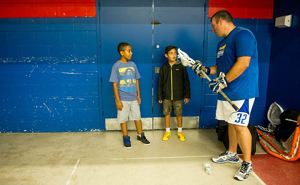 A man with a lacrosse stick talking to two boys