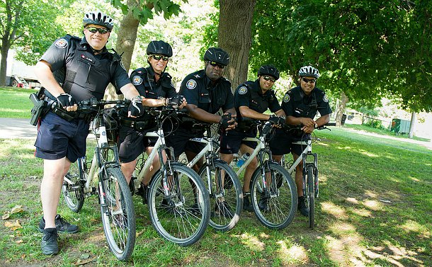 Four men and one woman in TPS uniform on bikes in a row in a treed area