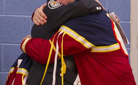 A man hugs a woman in TPS uniform