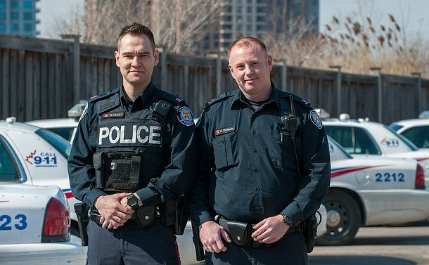 Two male constables in uniform looking into the camera and smiling. They are standing outside in a police parking lot with patrol cars behind them.