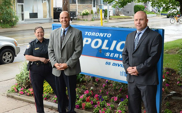 A woman in TPS uniform stands with two men beside a TPS sign